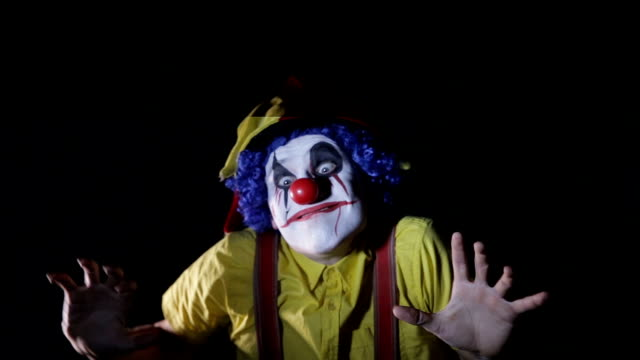 Scary shot of a spooky mad clown making frightening faces in dark room under stroboscope. Portrait video