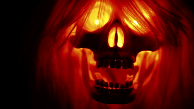 Scary skull with hair flying, spooky halloween background on black video