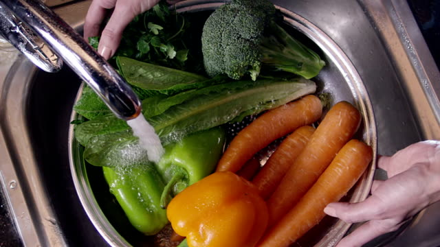 Scene of washing fresh vegetables. broccoli, pepper and carrots. Under the tap. video