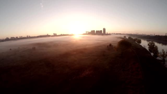 Scenic aerial of the fog clouds towards the sun on the field and river. Thick fog lying on fields, forests, hills and roads. Misty weather, birds point of view. Sunset, sunrise. Epic aerial over clouds and fogs. video