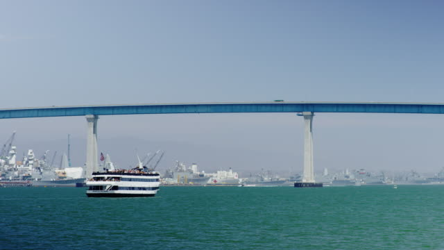 Scenic real time action video of the Spirit of San Diego cruise ship crossing the San Diego Bay under the Coronado Bridge in California. Stock color video shot 6k by RED Dragon digital camera. video