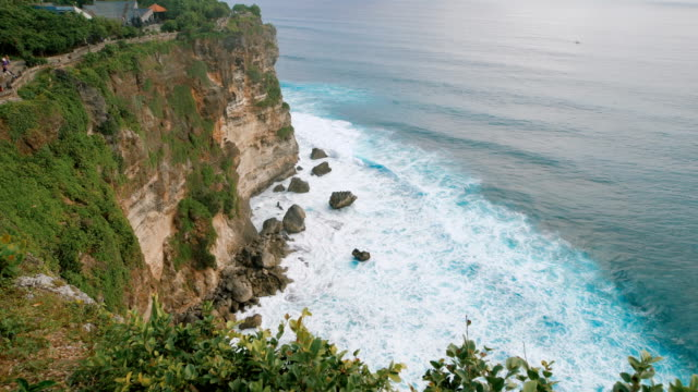 Scenic view of high cliff and deep blue sea at the foot of the rock. Breathtaking panoramic scene of high mountain view and endless water surface of the ocean video