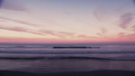 Scenic wide-angle surf shot of wave breaking on a colorful horizon at sunset.Original stock color video shot in 6K by a RED Dragon camera. video