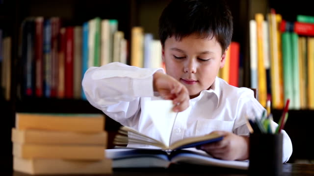 school boy reading and thinking with a smile video