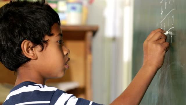 School Boy working out a Math sum video