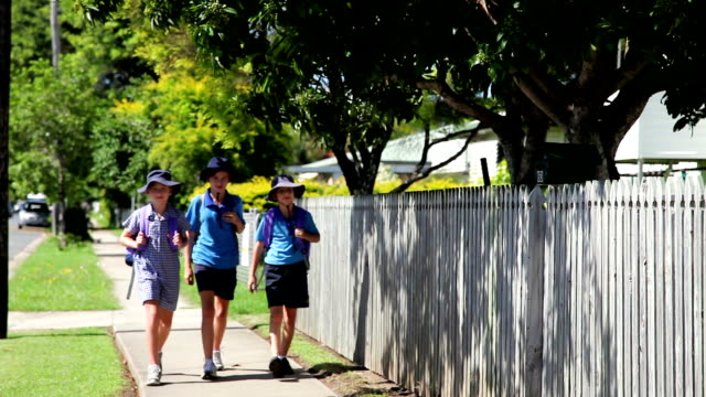 School children girls in uniform walking on footpath towards camera video