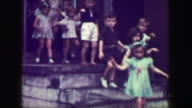1949: School children leaving class down steep slippery concrete staircase, no handrail. video