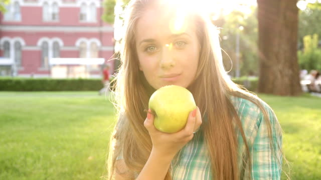 School girl eating apple and looking at camera video