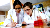 School girls writing in journal book while experimenting in laboratory at school video