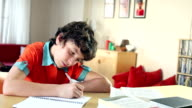 School kid does his homework looks up and smiles video