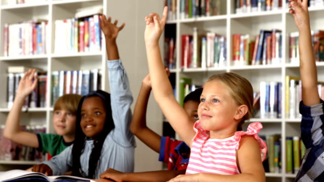 School kids raising hand in library video