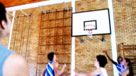 School students playing basketball in basketball court video