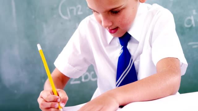 Schoolboy doing his homework in classroom video