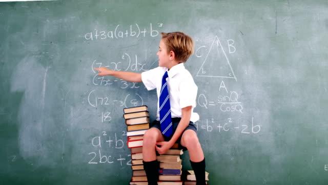 Schoolboy solving maths formula on chalkboard video