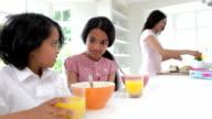 Schoolchildren Having Breakfast Whilst Mother Makes Lunch video