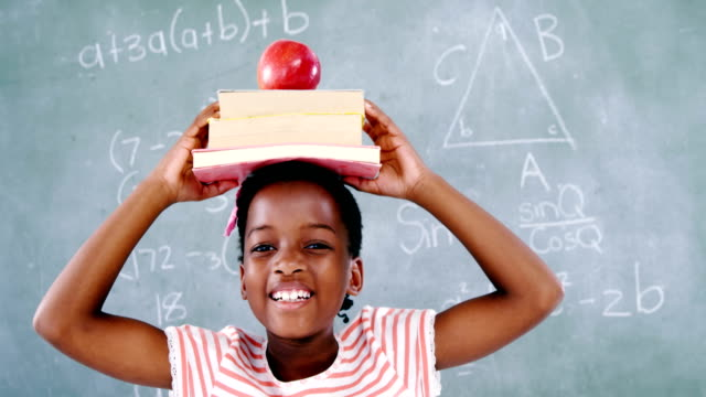 Schoolgirl holding books stack with apple on head against chalkboard video
