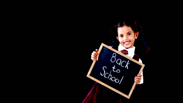 Schoolgirl holding slate with text against black background video