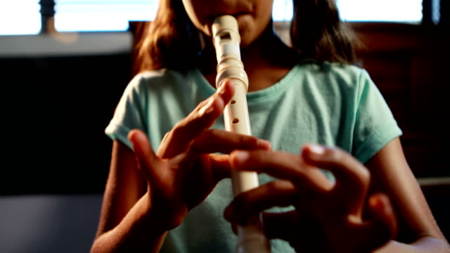 Schoolgirl playing flute in music class 4k video
