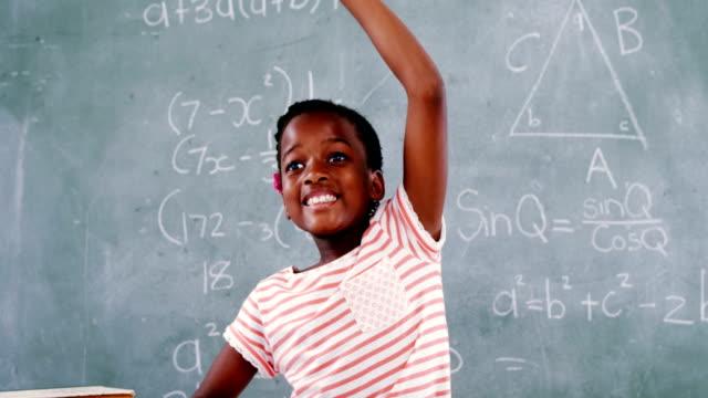 Schoolgirl raising hand while sitting in classroom video