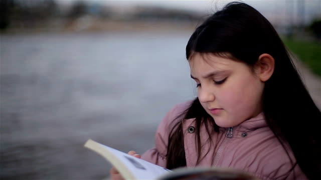 schoolgirl reading book in nature video