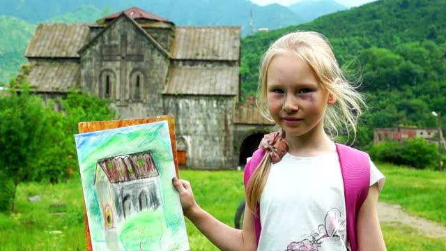 Schoolgirl showing her drawing outdoors video