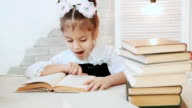 Schoolgirl sitting at a table and the reading a book, while reading it yawns. video