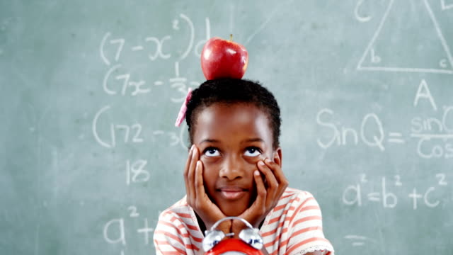 Schoolgirl sitting with red apple on her head against chalkboard video