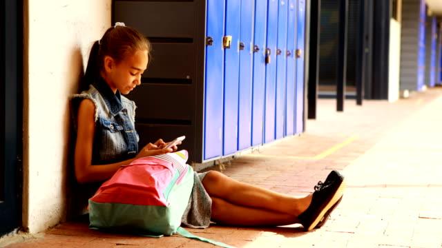 Schoolgirl using mobile phone in locker room 4k video