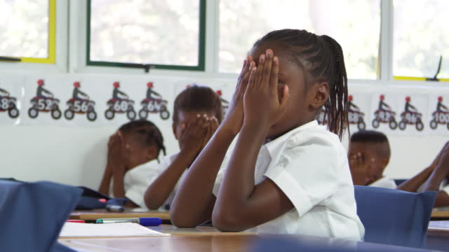 Schoolgirl with head in hands at lesson at elementary school video