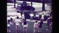 1949: Schoolmarm teacher playing Hooky Pooky childhood game in house front yard. video