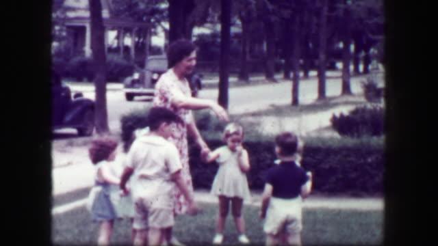 1949: Schoolmarm teacher playing kids front yard holding hands. video
