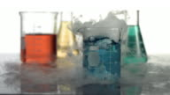 Science beaker bubbling and smoking, slow motion video