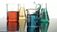 Science beaker splash, slow motion video