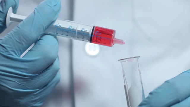 Science lab technician filling test tube with red liquid video