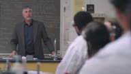 A science professor answers questions from the front of the classroom video