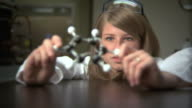 Science student studying molecule model video