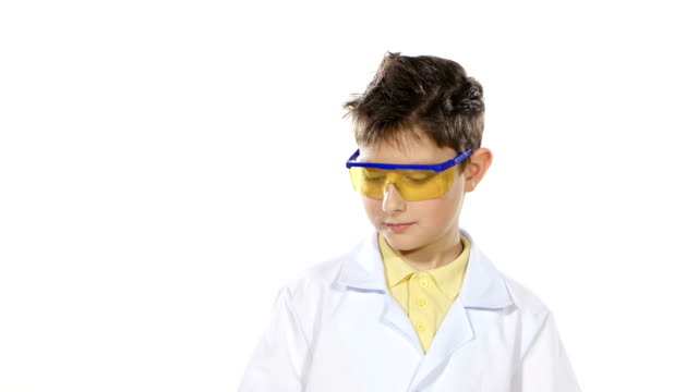 Scientist boy in uniform and protective glasses with test tubes, evaluates, isolated on white background video
