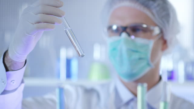 Scientist, doctor, student, in clean suit examining sample in test tube video