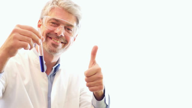 A scientist explaining something about two test tubes and shows on a white wall. He shows a thumb up at the end video