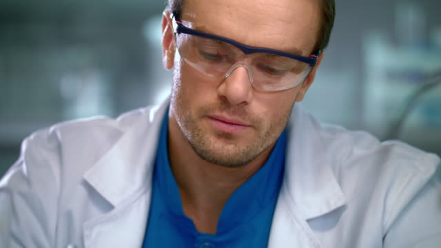 Scientist face. Portrait of researcher working in safety glasses video