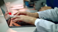Scientist hand typing on laptop. Close up of female scientist hands on laptop video