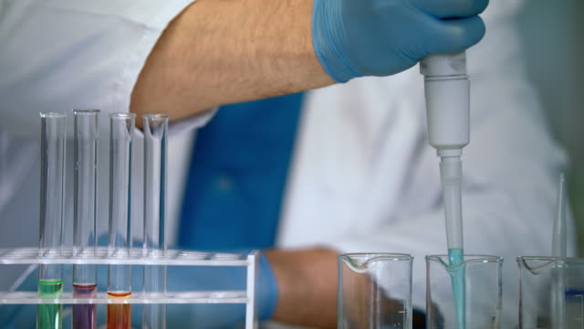 Scientist hands pouring liquid samples into test tubes. Laboratory equipment video