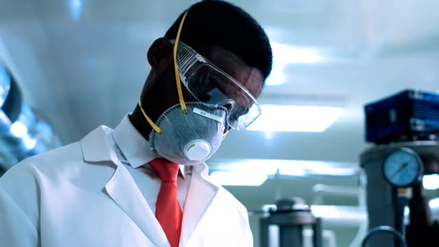 Scientist in mask writing in lab video