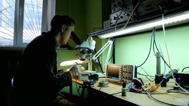 Scientist in the lab looking into a microscope video