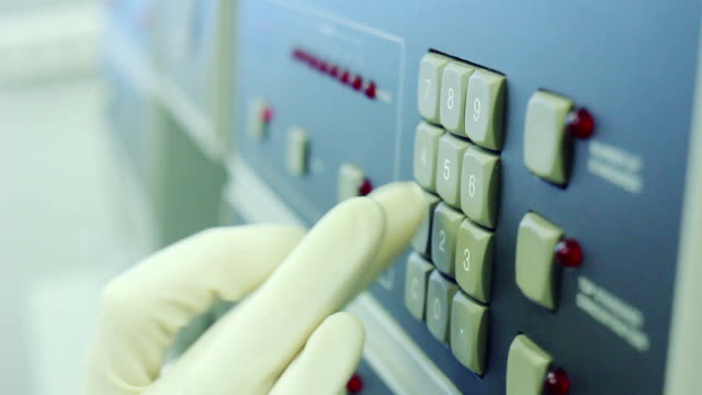 Scientist in white glove is clicking on hardware buttons of equipment video