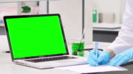 Scientist is writing notes with green screen laptop video