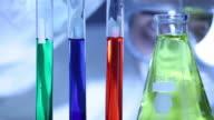 Scientist looks at test tubes video