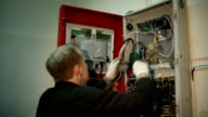 Scientist makes electrical measurements in the switchboard video