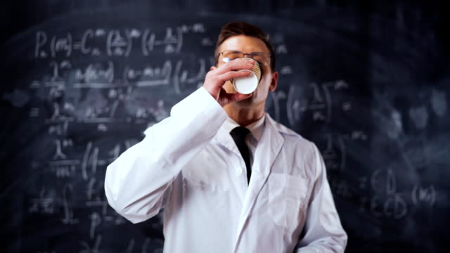 Scientist man in white work robe near chalk board with equations drinks coffee video