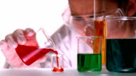 Scientist pouring red liquid into beaker video